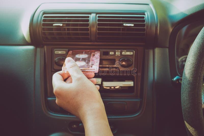 La main de femme tenant la cassette de bande dans la voiture pour conduire écoutent musique photos libres de droits