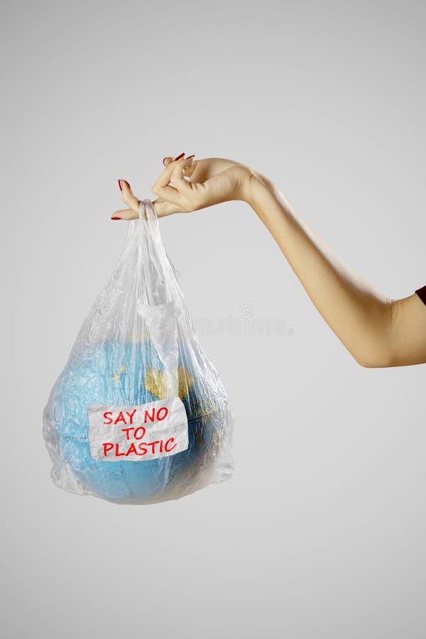 La main de femme tient le globe de la terre dans un sachet en plastique photographie stock libre de droits
