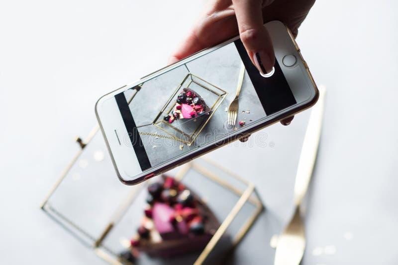 La main de la fille avec le morceau de photographies de téléphone de gâteau savoureux images stock