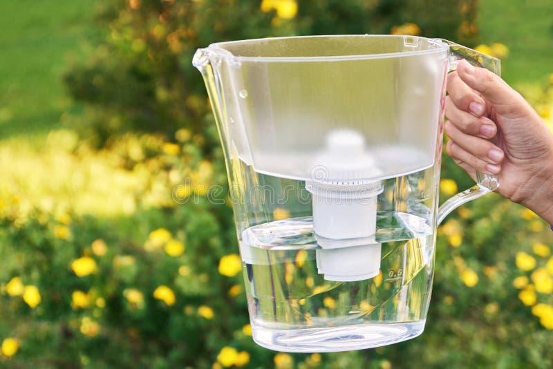 La main de la fille tient une cruche de filtre d'eau dans le jardin ensoleillé d'été avec les fleurs jaunes sur le fond photo stock