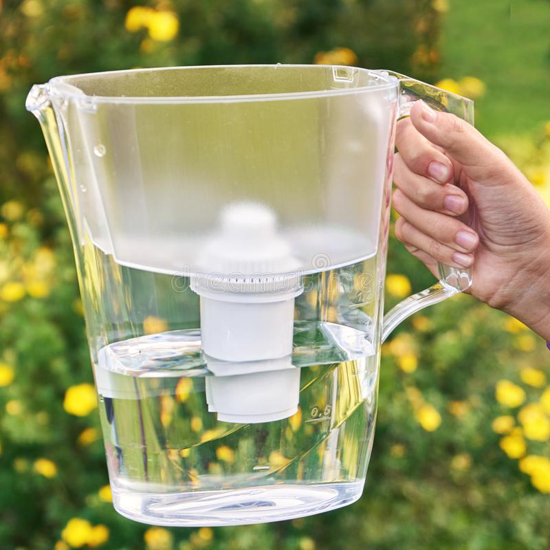 La main de la fille tient une cruche de filtre d'eau dans le jardin ensoleill? d'?t? avec les fleurs jaunes sur le fond photos stock