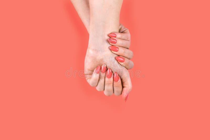 La main de la jeune femme avec la manucure de corail parfaite image stock