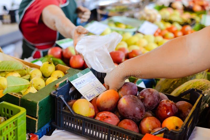 La main de l'acheteur prenant la mangue près du prix à payer dedans image stock