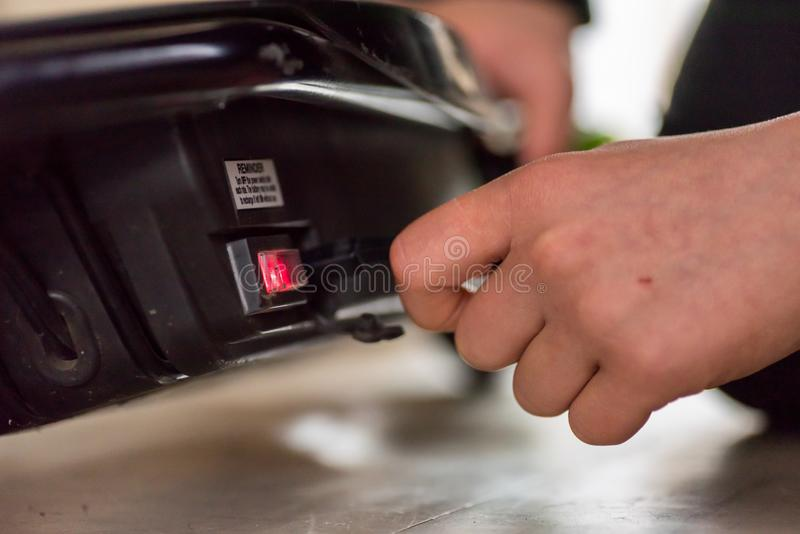 La main de l'adolescence de vue de jour de plan rapproché branchent dedans le câble de remplissage au scooter électrique images libres de droits