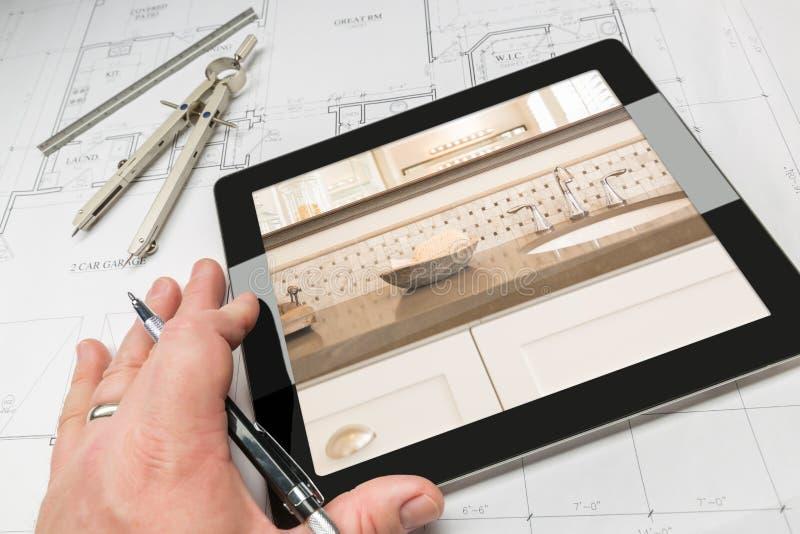 La main de l'architecte sur la Tablette d'ordinateur montrant la salle de bains détaille l'OV images stock