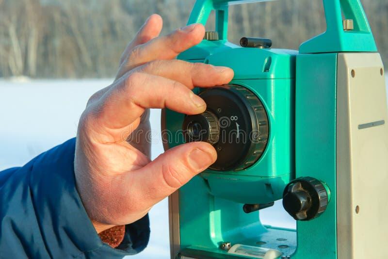 La main de l'arpenteur a installé la station totale pour l'opération images stock