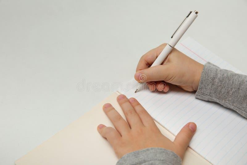 La main de l'enfant écrit dans un carnet sur le fond blanc image stock