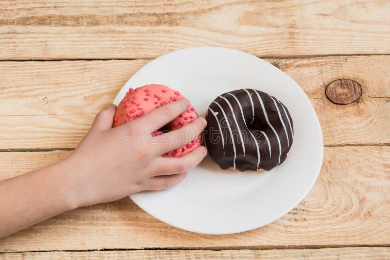 La main de l'enfant atteint des butées toriques Nourriture savoureuse pour des enfants avoir l'amusement avec le beignet images libres de droits