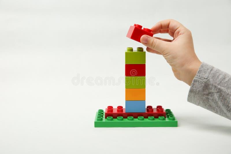La main de l'enfant compile une pyramide des cubes colorés image stock