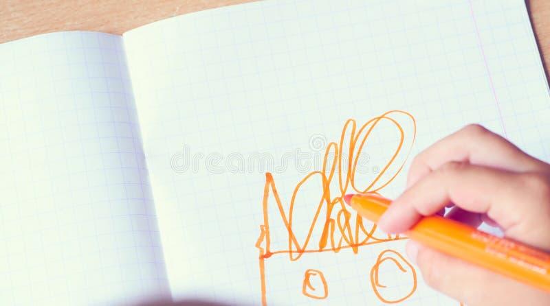 La main de l'enfant dessine dans un carnet avec le stylo feutre orange Créativité du ` s d'enfants images stock