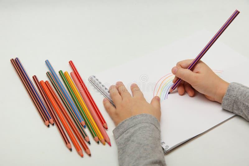 La main de l'enfant dessine un arc-en-ciel avec les crayons colorés sur un fond blanc images stock