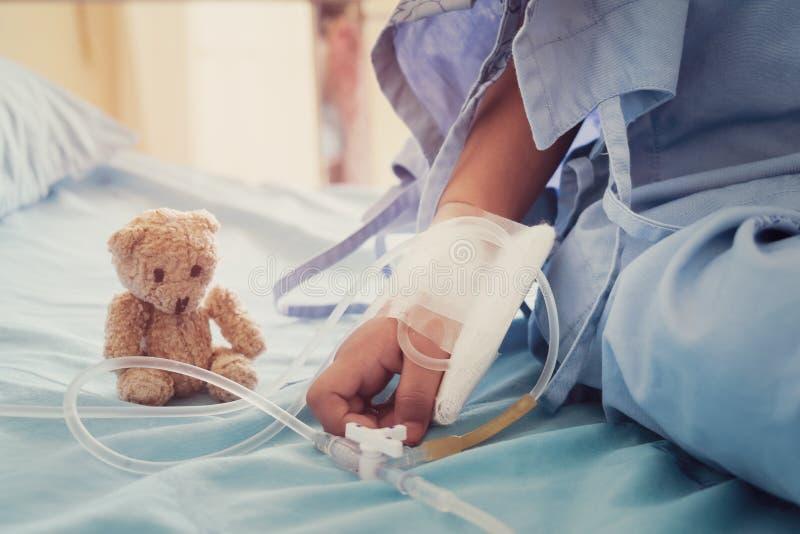 La main de l'enfant de participation de mère qui patients de fièvre dans l'hôpital au gi photo stock