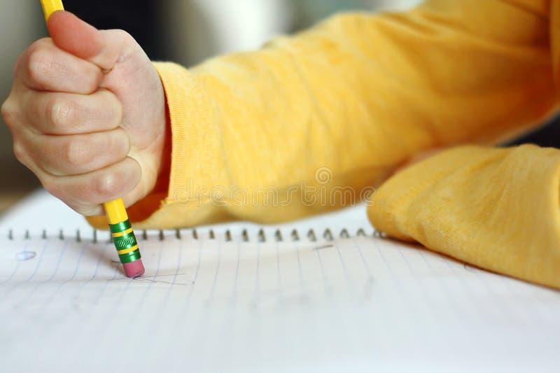 La main de l'enfant s'effaçant avec le crayon sur le papier de carnet images stock
