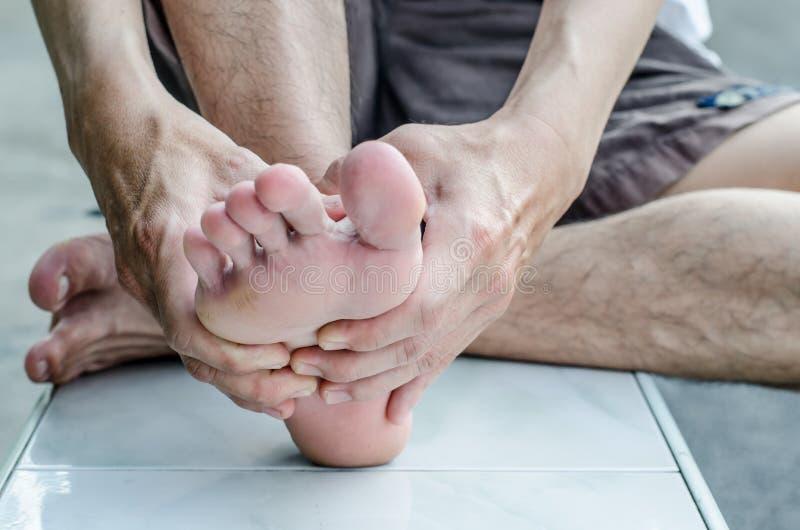 La main de l'homme étant massée un pied photos stock
