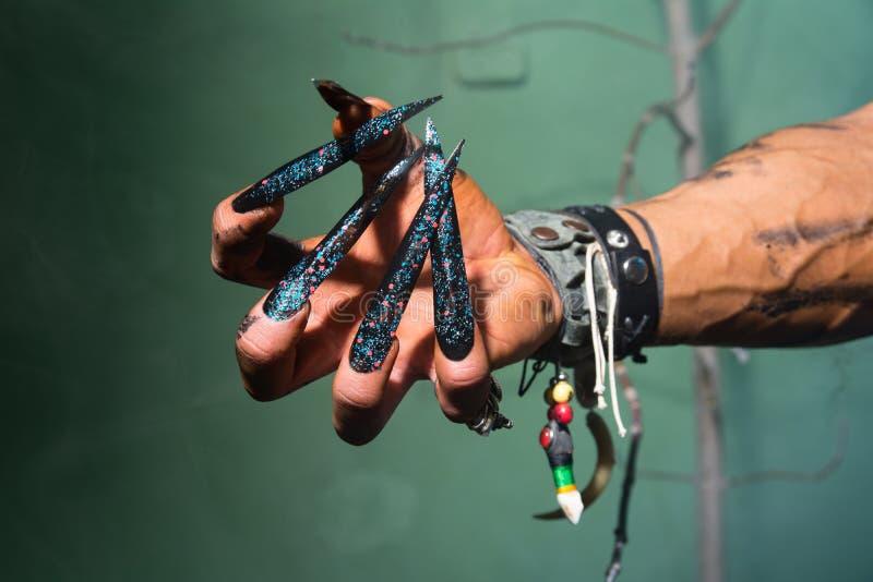 La main de l'homme avec de longs clous hors d'un cauchemar photographie stock