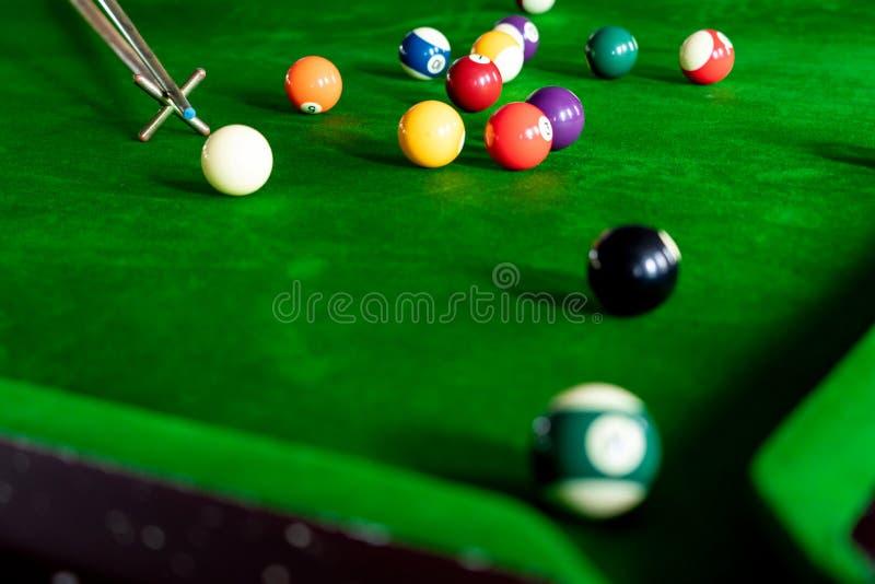 La main de l'homme et le bras de queue jouant le jeu de billard ou préparant viser à tirer des boules de piscine sur une table de image libre de droits