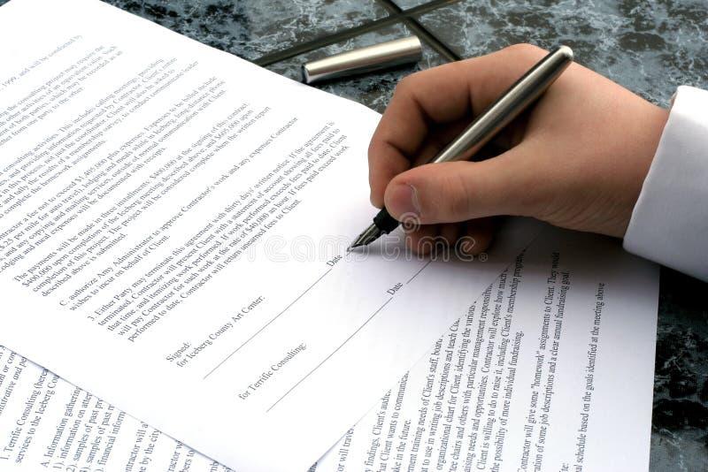La main de l'homme retenant un crayon lecteur écrivant une signature photo stock