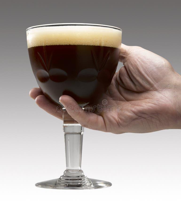 La main de l'homme retenant une bière de Trappist image stock