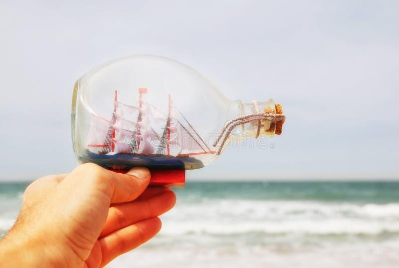 La main de l'homme tenant le bateau décoratif dans la bouteille devant l'horizon de mer Vintage filtré photos libres de droits