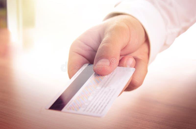 La main de l'homme tenant une carte de crédit photographie stock libre de droits
