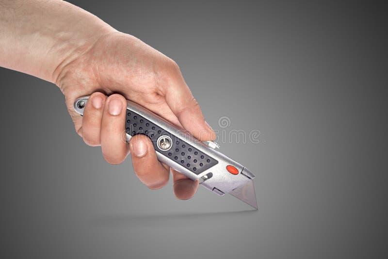 La main de l'homme tenant une papeterie de couteau image libre de droits