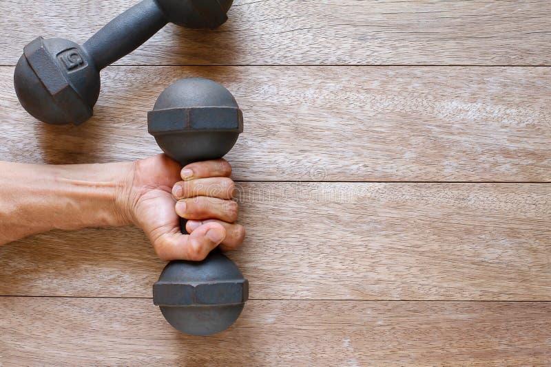 La main de l'homme tenant la vieille haltère rouillée sur le plancher en bois de cru photographie stock