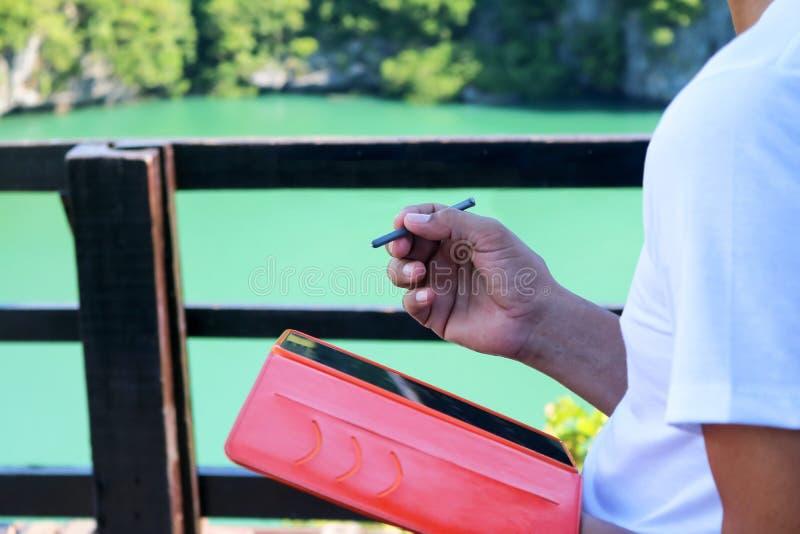 La main de l'homme utilisant le comprimé graphique avec l'outil numérique de stylo pour la conception dans le jardin de nature photographie stock