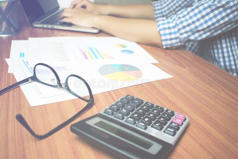 La main de l'homme utilise une chemise de plaid bleue travaille sérieusement sur le bureau argent de concepts de calculatrice d'a photo stock