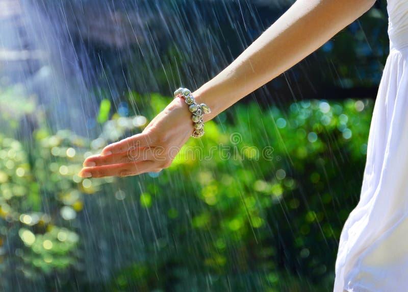 La main de la femelle sous les gouttes de pluie images stock