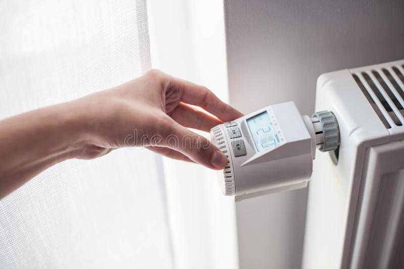 La main de la femme ajustant la température image libre de droits