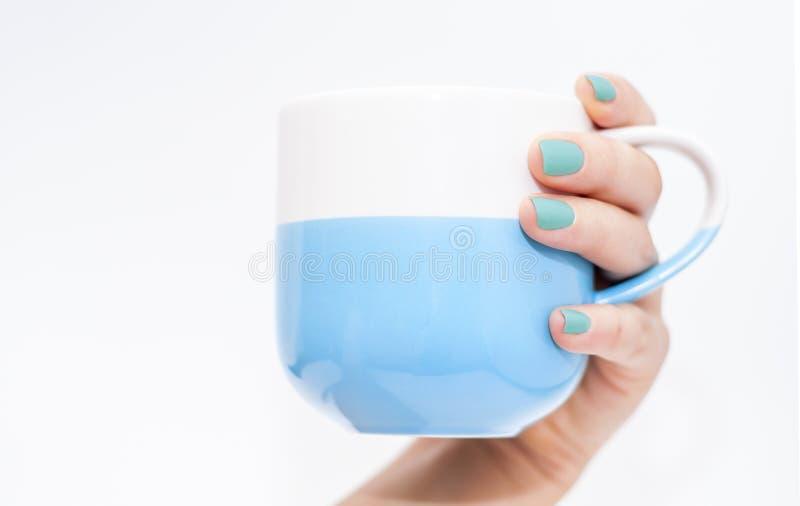 La main de la femme avec les clous bleus tenant une tasse bleue images libres de droits