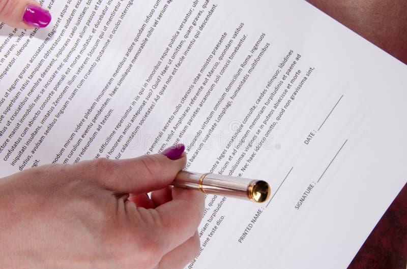 La main de la femme présentant à un stylo pour le signe un exposé image stock