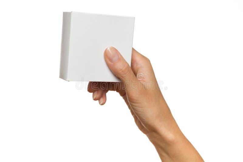 La main de la femme tenant le boîtier blanc images stock
