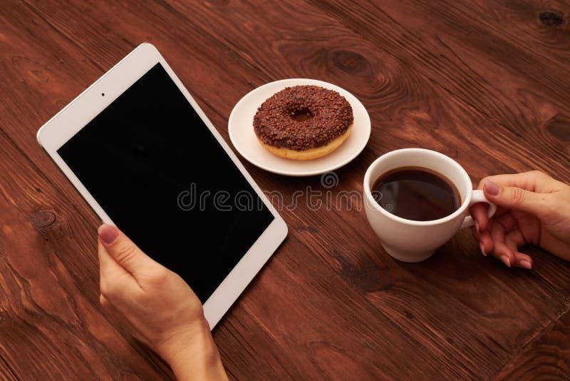 La main de la femme tenant le PC de comprimé et la tasse de café sur la table en bois photo libre de droits