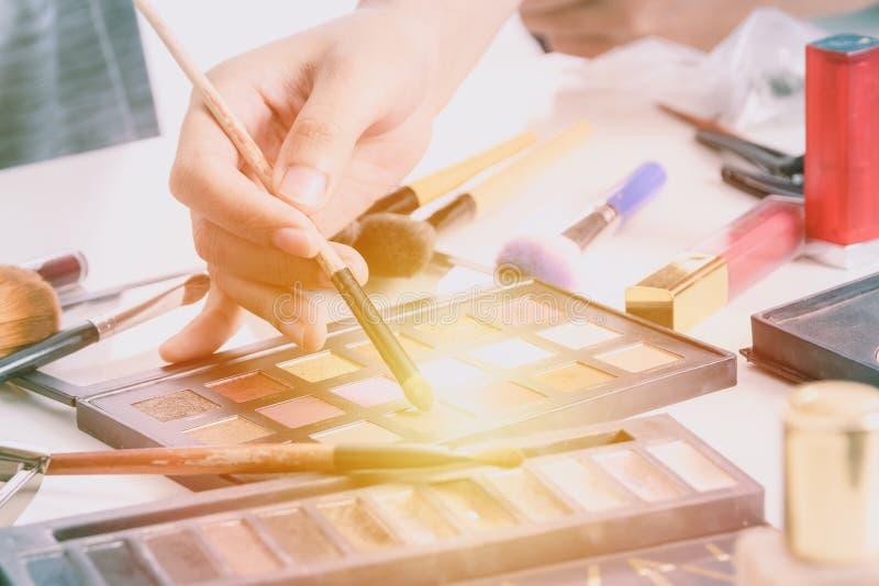 La main de maquilleur utilisant des brosses saupoudrent la base et les outils de composent l'artiste image stock