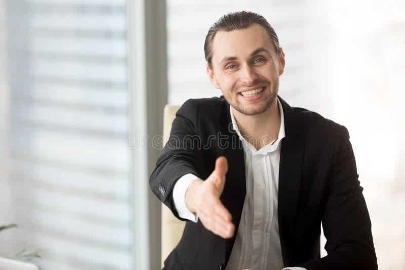 La main de offre de sourire amicale d'homme d'affaires pour saluer ou conviennent photo libre de droits