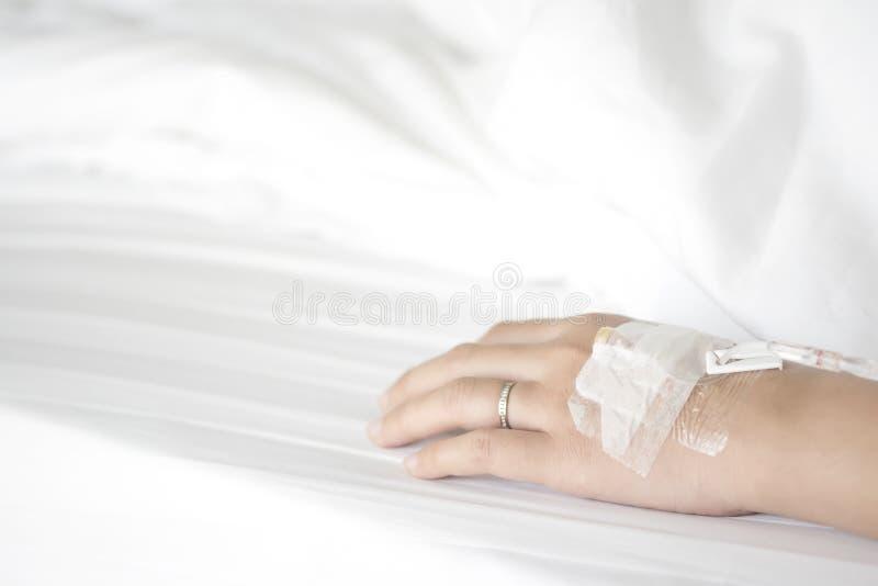 La main de la patiente mariée de femme recevant la solution saline par l'intrav photo libre de droits