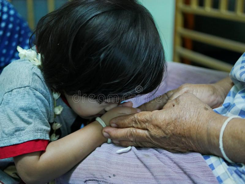 La main de personne âgée tenant d'un petit les mains bébé tandis que le bébé faisant le wai, payant le geste de respect, au photos libres de droits