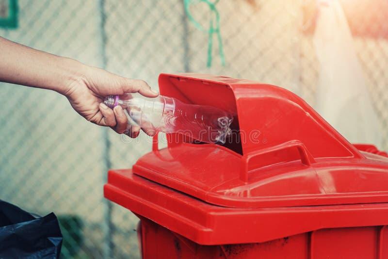 la main de personnes tenant le plastique de bouteille de déchets mettant dans réutilisent la poubelle pour le nettoyage photographie stock