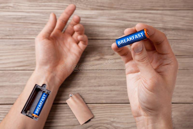 La main de petit déjeuner de l'homme avec la fente pour les batteries de remplissage déjeunent photos stock