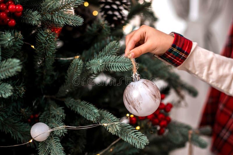 La main de petit enfant décorant l'arbre de Noël à l'intérieur photos stock