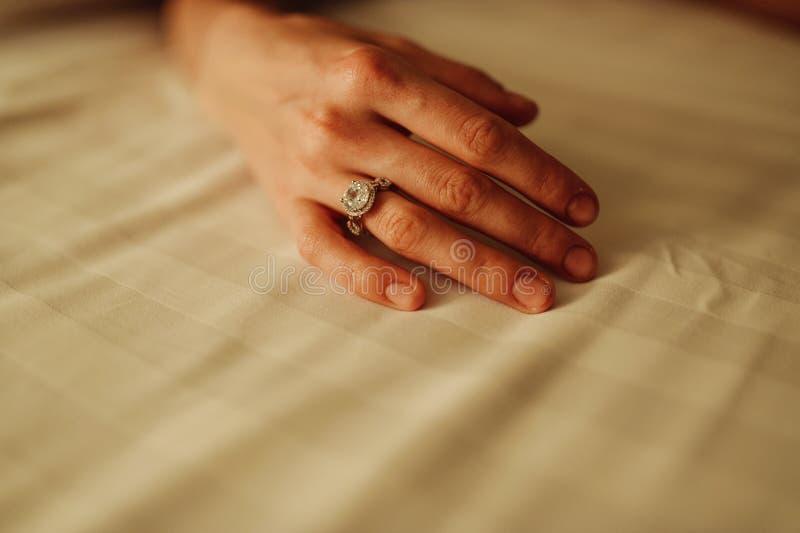 La main de plan rapproché de la jeune femme avec la manucure a poli des ongles utilisant une bague de fiançailles chère image libre de droits