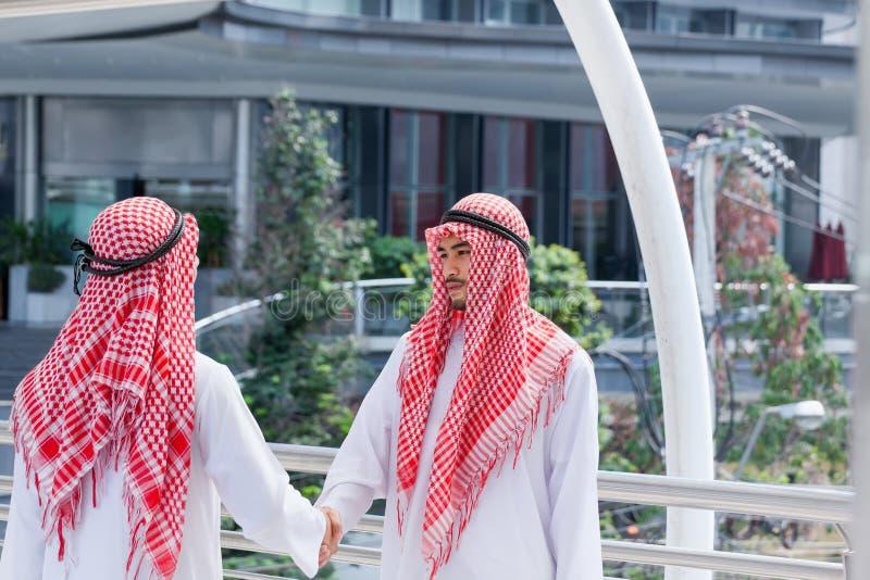 La main de secousse d'homme d'affaires de deux Arabes et prennent la décision ensemble dedans image stock