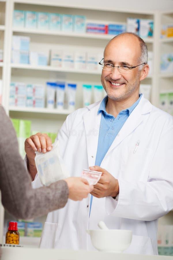 La main des clients versant l'argent sur le pharmacien masculin For Medicine photo stock