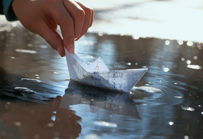 La main des enfants de l'écolier lance un petit bateau de papier fait image libre de droits