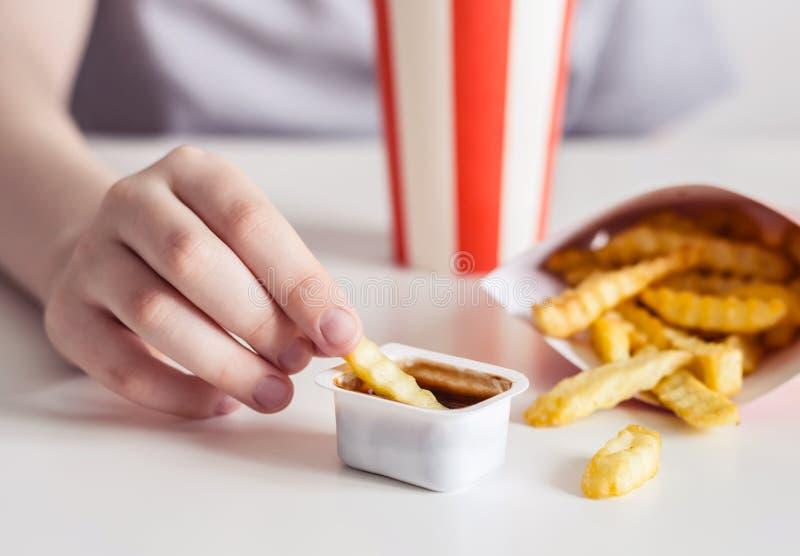 La main des enfants trempe des pommes frites en plan rapproché de sauce barbecue, foyer sélectif images stock