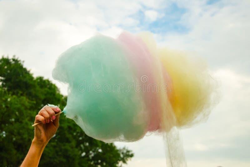 La main des femmes tenant la sucrerie de coton colorée dans le backgrou photos libres de droits