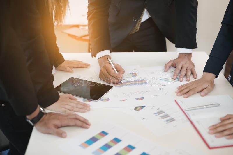 La main des hommes d'affaires écrivent des diagrammes de document d'entreprise au DES de bureau images stock