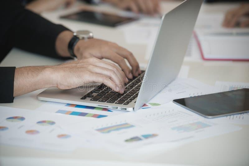 La main des hommes d'affaires a utilisé l'ordinateur portable tandis que groupe discutant sur le stockm images stock