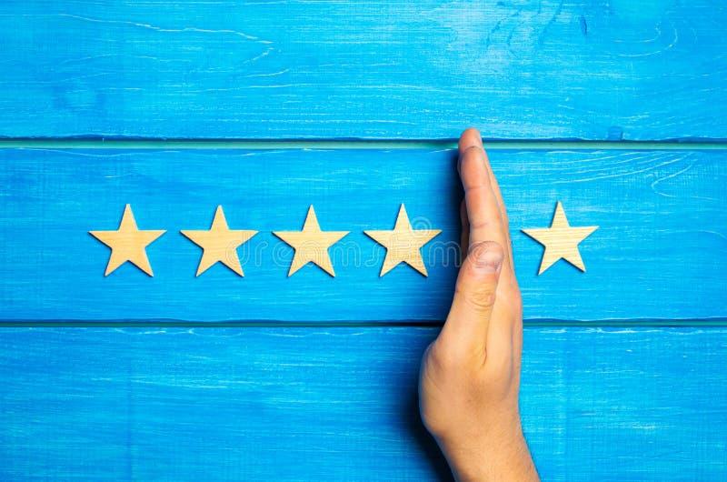 La main divise la cinquième étoile des quatre autres Évaluation de 5 étoiles, 4 étoiles Aperçu de restaurant, hôtel, café image libre de droits